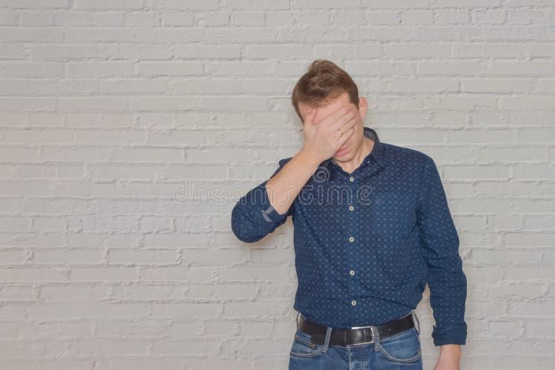 Un homme en chemise fait des gestes au mur de briques blanches un endroit pour une étiquette image libre de droits