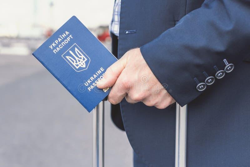 Un homme en costume bleu avec une valise et un passeport ukrainien à l'aéroport Concept de voyage d'affaires photo libre de droits