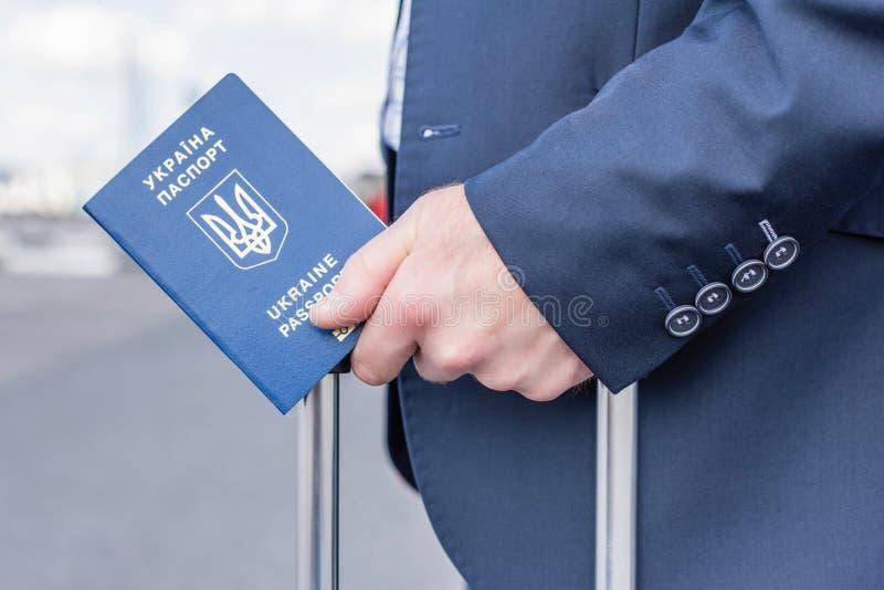 Un homme en costume bleu avec une valise et un passeport ukrainien à l'aéroport Concept de voyage d'affaires image libre de droits