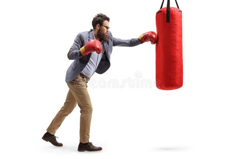 Un homme en tenue officielle frappe un sac de boxe photographie stock libre de droits