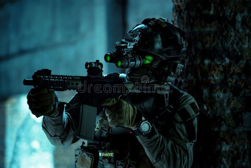 Un homme en uniforme avec une mitrailleuse et allumé le dispositif de vision nocturne à l'intérieur d'un bâtiment cassé Soldat so photographie stock