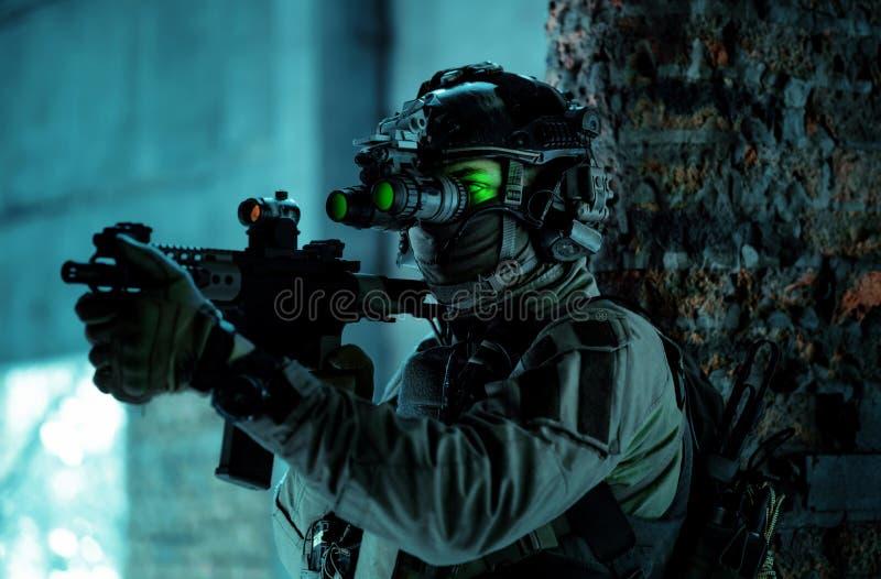 Un homme en uniforme avec une mitrailleuse et allumé le dispositif de vision nocturne à l'intérieur d'un bâtiment cassé Soldat so image libre de droits