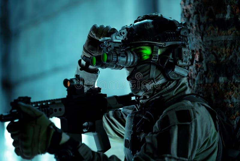 Un homme en uniforme avec une mitrailleuse et allumé le dispositif de vision nocturne à l'intérieur d'un bâtiment cassé Soldat de images stock