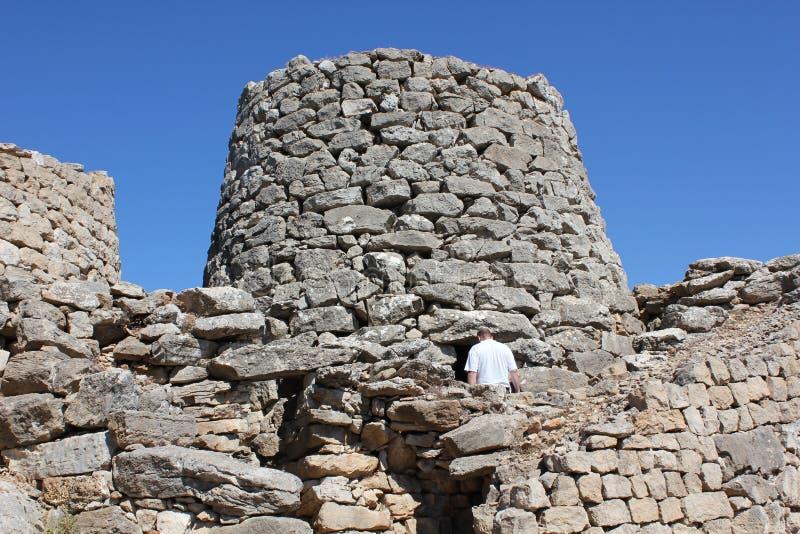 Un homme entrant dans un Nuraghe, un bâtiment antique typique de roche de l'île de la Sardaigne photo stock
