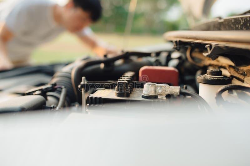 Un homme essaye de réparer la voiture sur la route photographie stock libre de droits