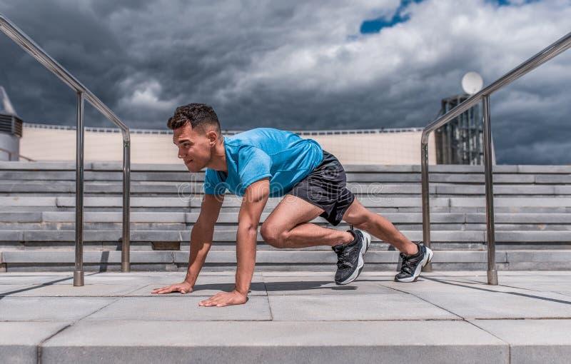 Un homme est un athlète, exercices abdominaux, les muscles, été dans la ville, étirant des muscles avant de pulser, formation de  photographie stock libre de droits