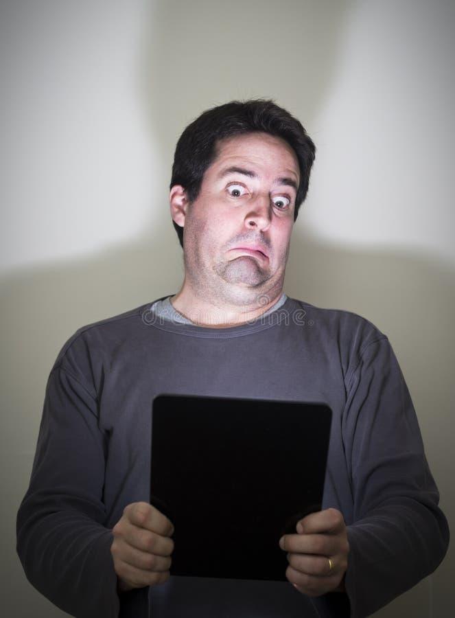 L'homme est horrifié par ce qu'il voit sur un comprimé numérique photos libres de droits