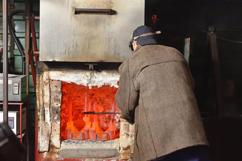 Un homme est un ouvrier, sort les parties chaudes d'un four électrique pour durcir le métal Un homme au travail dangereux avec photos libres de droits