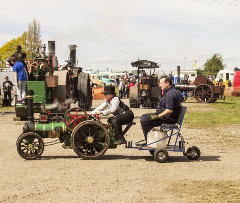 Un homme et un enfant sur une machine à vapeur très petite photographie stock libre de droits