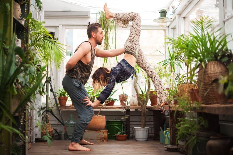 Un homme et les femmes pratiquent des asanas de yoga en serre chaude avec des fleurs Paires de yoga photo stock