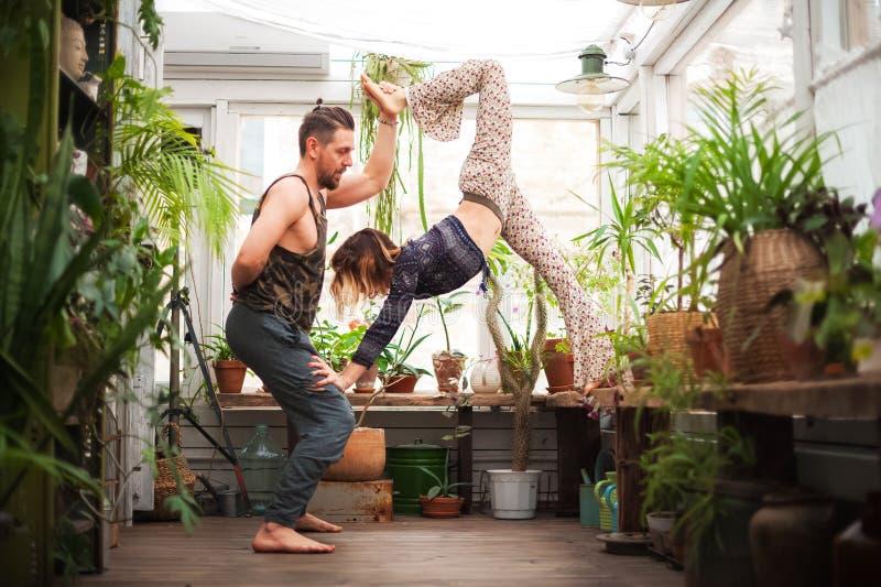 Un homme et les femmes pratiquent des asanas de yoga en serre chaude avec des fleurs Paires de yoga image libre de droits