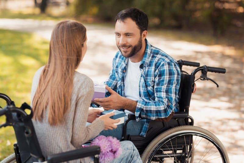 Un homme et une femme dans des fauteuils roulants se sont réunis en parc Ils échangent des cadeaux et le sourire à l'un l'autre image libre de droits