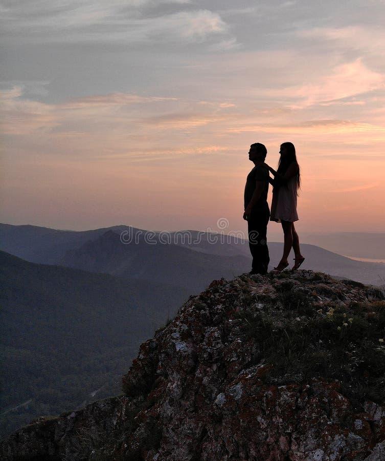 Un homme et une femme se tiennent sur la montagne au coucher du soleil photographie stock