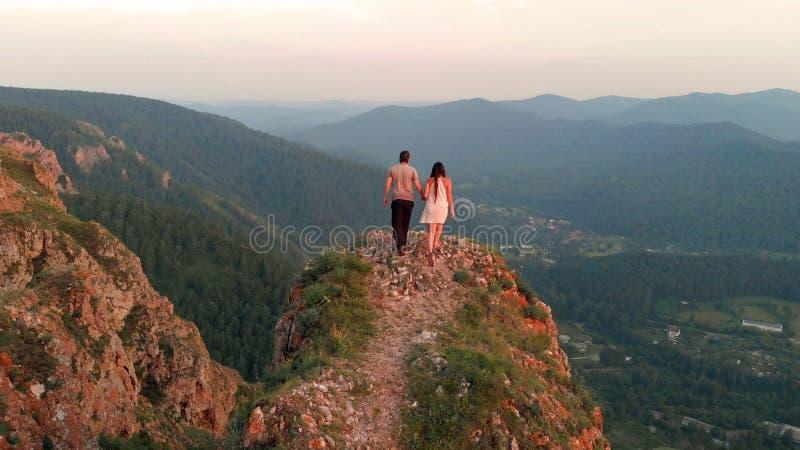 Un homme et une femme se tiennent sur la montagne au coucher du soleil photo stock