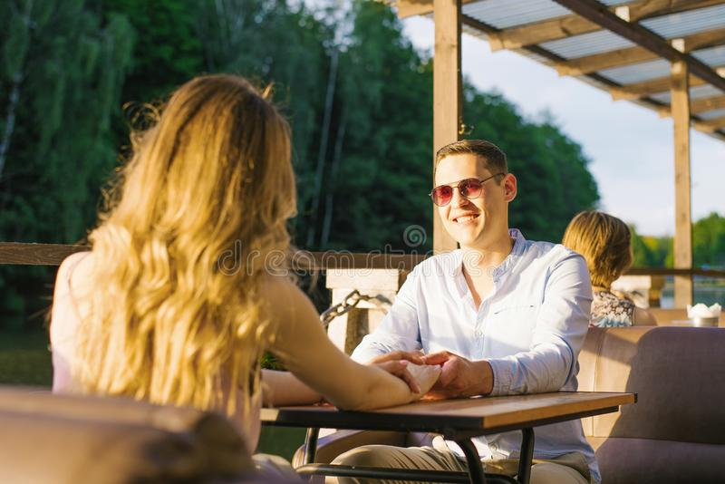 Un homme et une fille en rendez-vous sont assis à une table dans un café de rue sur le lac Ils sont heureux photographie stock
