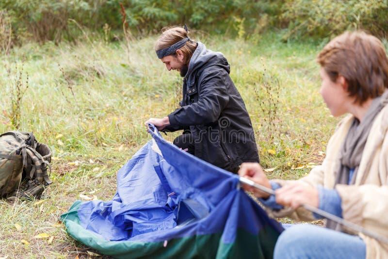 Un homme et une fille ont mis une tente dans les bois images libres de droits
