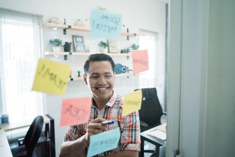 Un homme a eu la bonne idée a ensuite lu un certain mot sur les notes de papier collent sur le mur de verre photographie stock