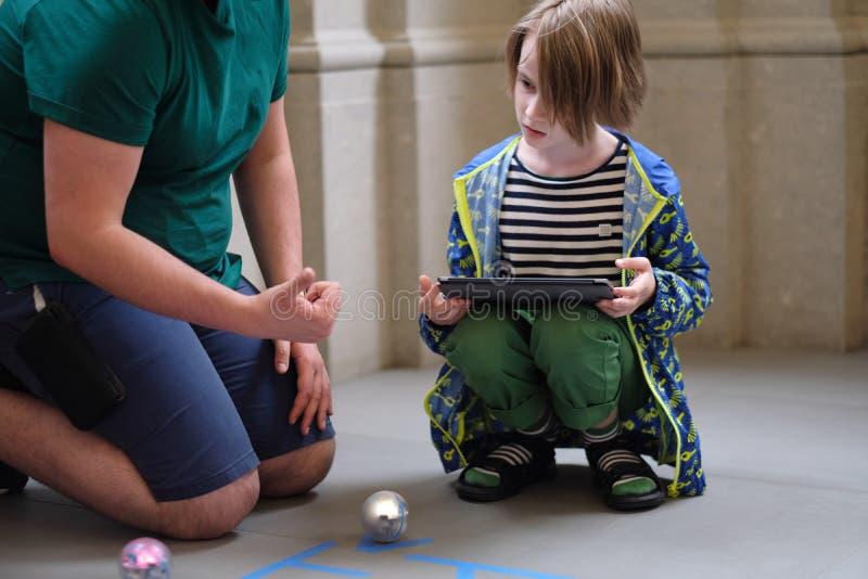 Un homme explique à un garçon les règles d'un jeu avec des robots photos libres de droits