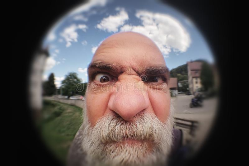 Un homme fâché regardant à une porte de trou images stock