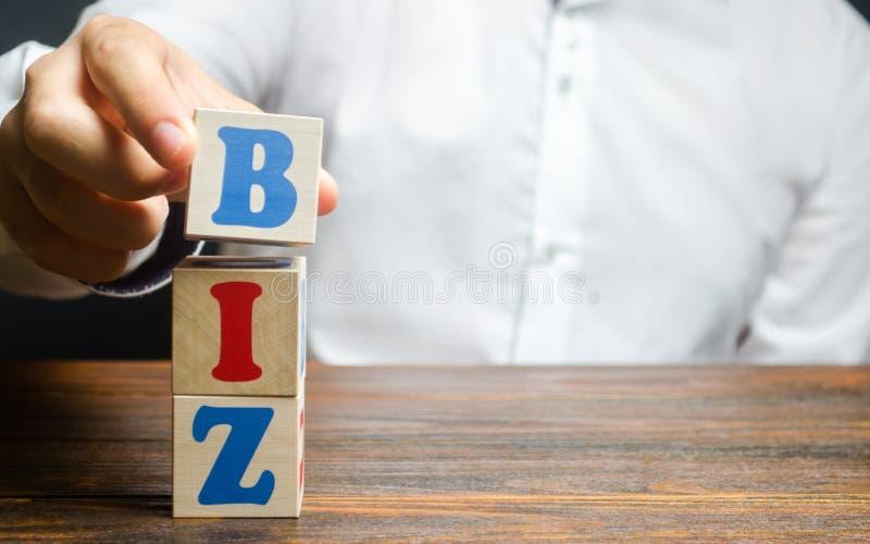 Un homme fait un mot BIZ à partir de blocs Création de sites sur le domaine de premier niveau pour les entreprises Promotion de l photos stock