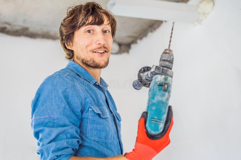 Un homme fait un trou dans le mur avec une perceuse image stock