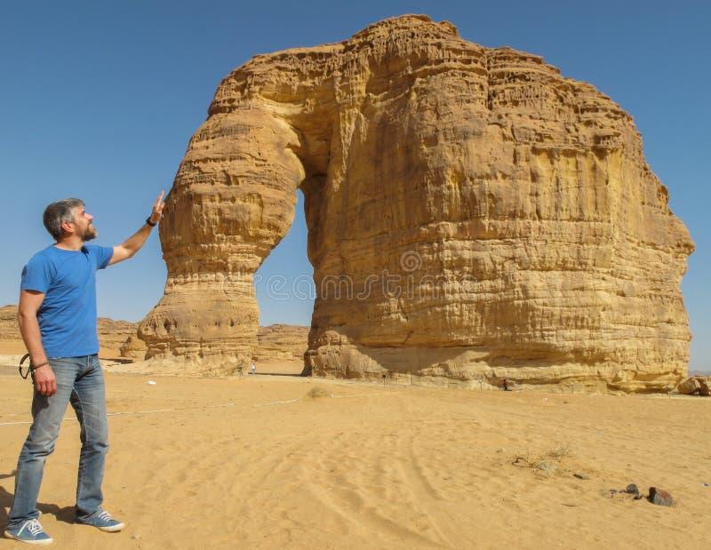 Un homme frottant la formation de roche connue sous le nom de roche d'éléphant en Al Ula, Saoudien Arabi KSA photo stock