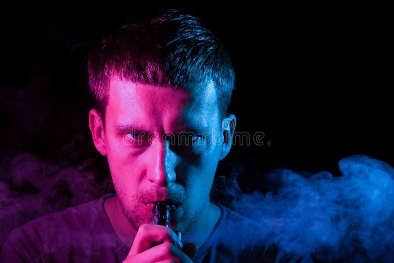 Un homme fume une cigarette et exhale la fumée colorée dans différentes directions sur un fond noir photos libres de droits