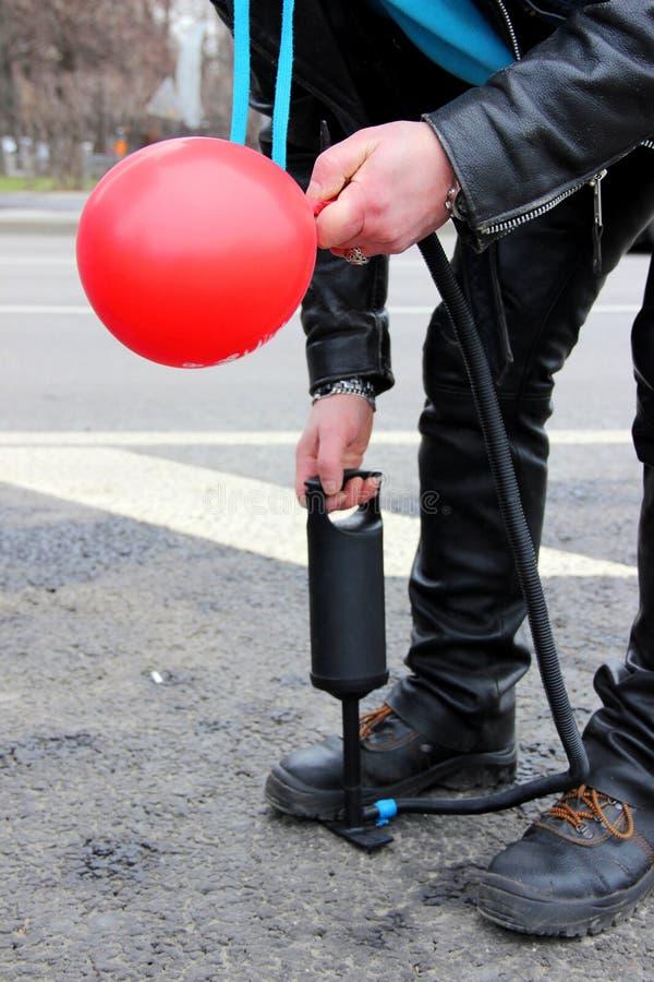 un homme gonfle un ballon rouge avec une pompe image stock