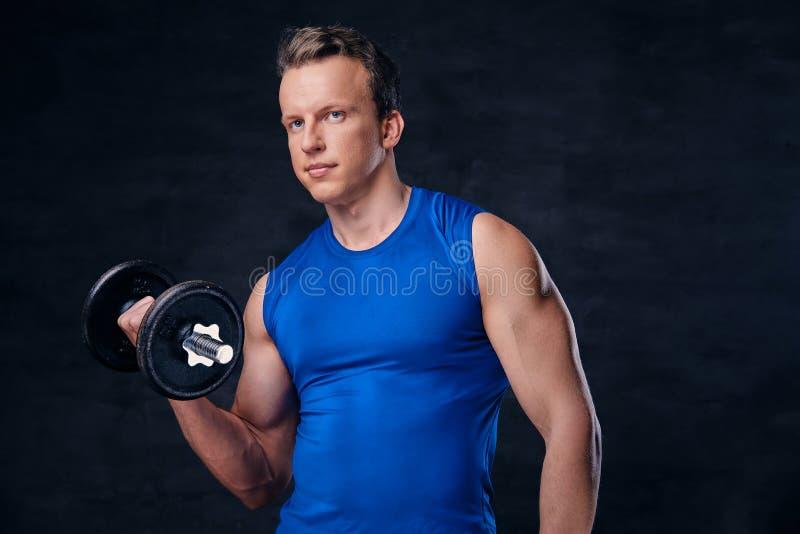 Un homme a habillé dans les prises bleues des vêtements de sport l'haltère au-dessus du fond gris-foncé photographie stock libre de droits
