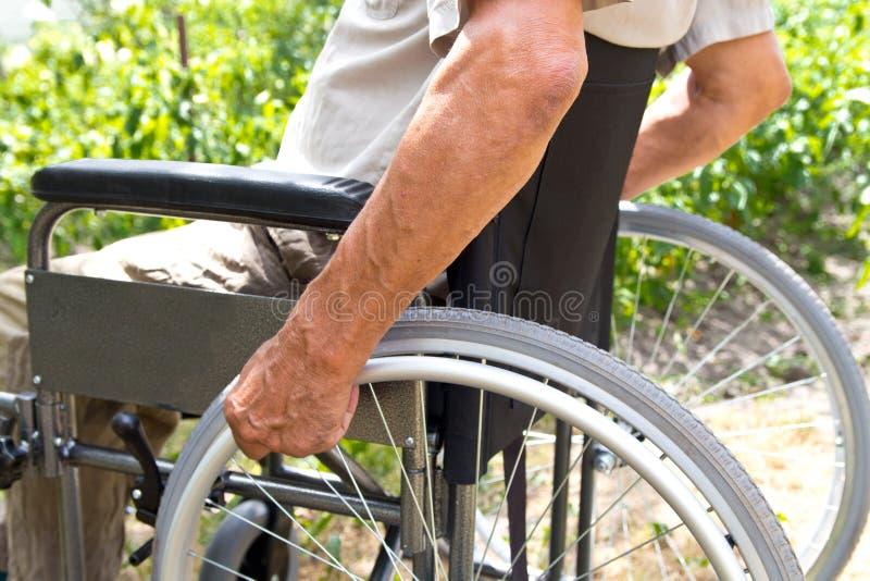 Un homme handicapé s'assied dans un fauteuil roulant, tient ses mains sur la roue Concept de personnes d'handicap photographie stock