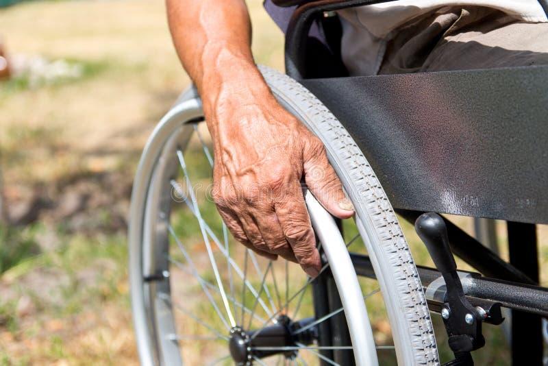 Un homme handicapé s'assied dans un fauteuil roulant, tient ses mains sur la roue Concept de personnes d'handicap images stock