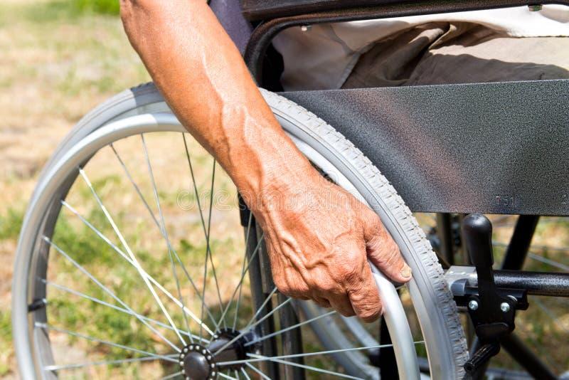 Un homme handicapé s'assied dans un fauteuil roulant, tient ses mains sur la roue Concept de personnes d'handicap image libre de droits