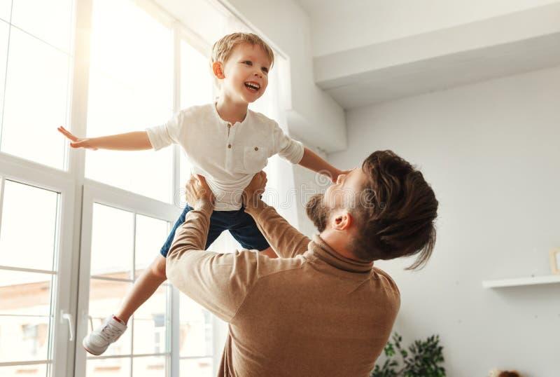 Un homme heureux avec un petit fils qui s'amuse à la maison images stock