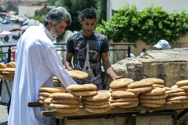 Un homme inspecte un chariot chargé avec du pain plat étant vendu à côté de la place de Lahdim dans Meknes au Maroc photographie stock libre de droits