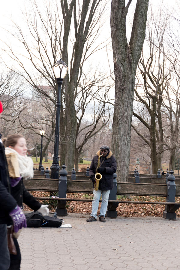 Un homme jouant un saxophone dans le Central Park à New York City images stock