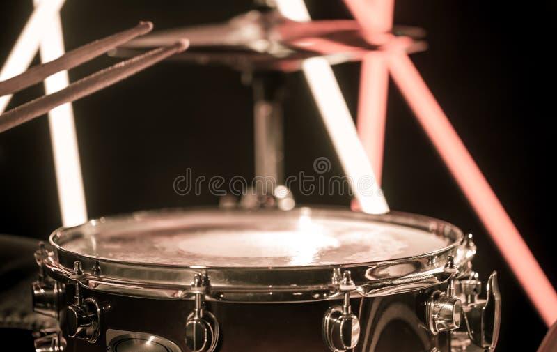 Un homme joue avec des bâtons sur un instrument de percussion musical, plan rapproché Sur un fond brouillé des lumières colorées photographie stock libre de droits