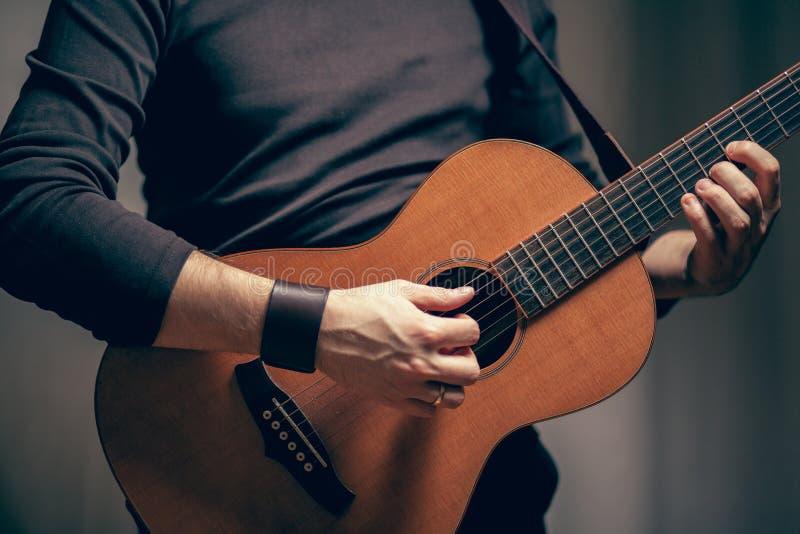 Un homme joue sur la guitare acoustique de vintage image stock