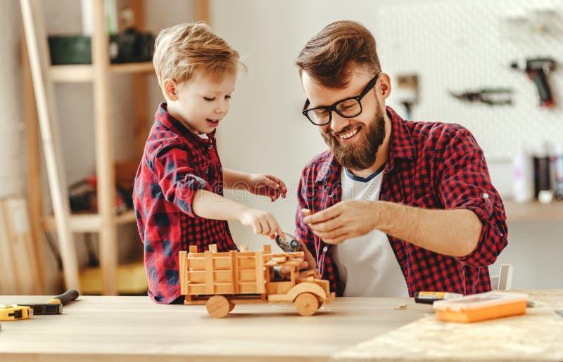 Un homme joyeux avec un enfant qui fait des jouets en bois dans un atelier photographie stock