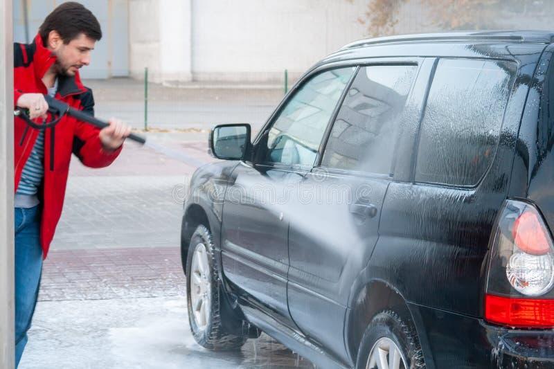 Un homme lave une voiture avec un jet fort de l'eau à une station de lavage de libre service photo stock