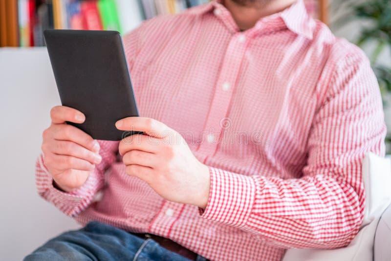 Un homme lisant un livre dans un lecteur d'ebook s'asseyant sur un divan ? la maison photos stock
