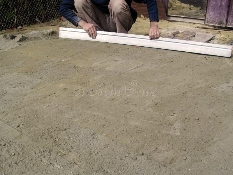 Un homme lisse la surface d'un mélange sec de sable-ciment au sol utilisant une règle de plâtrage images libres de droits