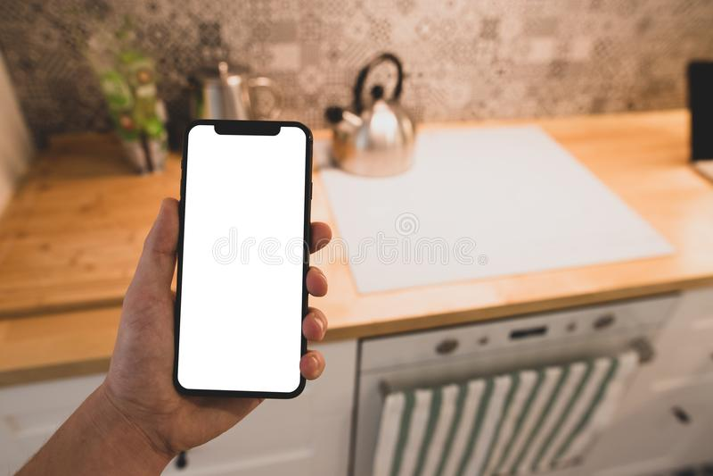 Un homme lit la recette sur un smartphone photo stock