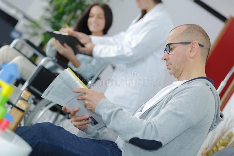 Un homme lit un magazine dans une salle d'attente médicale images stock