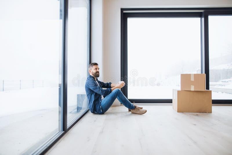 Un homme mûr avec des boîtes en carton se reposant sur le plancher, nouvelle maison de fourniture photographie stock libre de droits