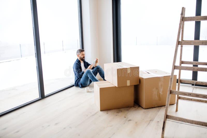 Un homme mûr avec des boîtes en carton se reposant sur le plancher, nouvelle maison de fourniture photos libres de droits