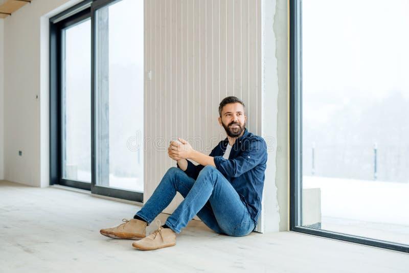 Un homme mûr avec la tasse de café se reposant sur le plancher, nouvelle maison de fourniture photo libre de droits