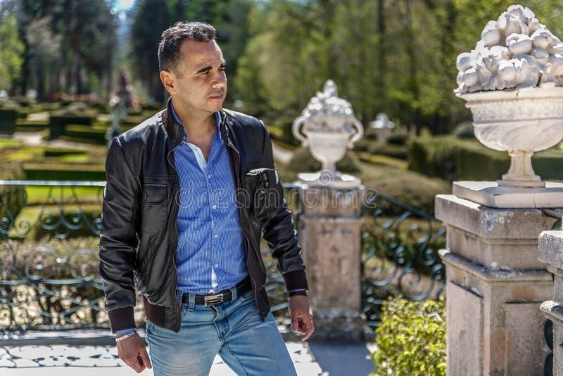 Un homme mûr dans une veste en cuir et regards bleus de chemise à quelque chose au milieu d'un parc photographie stock