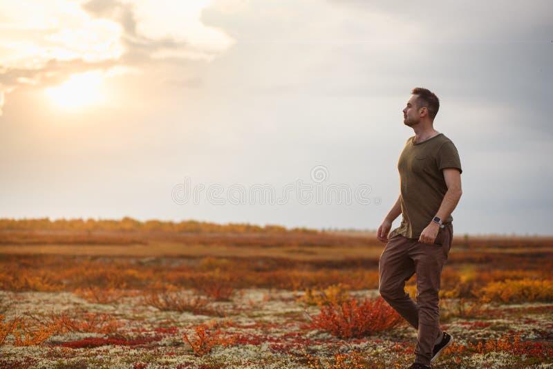 Un homme magnifique se reposant dans la toundra d'automne au coucher du soleil L'unité avec la nature images stock