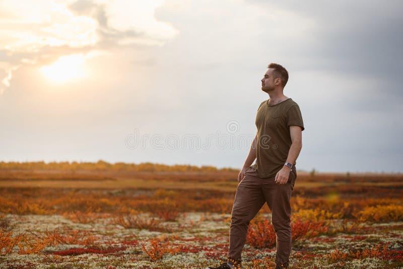 Un homme magnifique se reposant dans la toundra d'automne au coucher du soleil L'unité avec la nature image stock