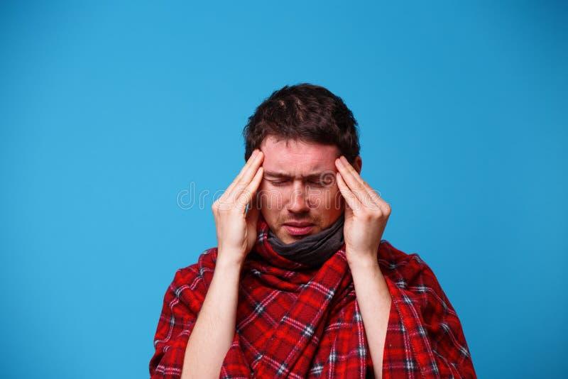 Un homme malade, enveloppé dans une couverture, tient sa tête Concept de maladie, de mal de tête et de migraine images stock
